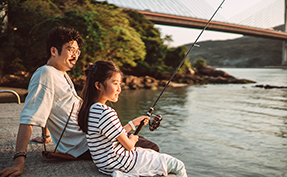 father and young daughter fishing on river