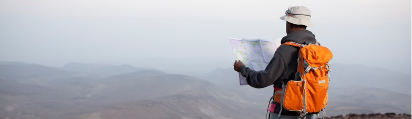 man hiking on mountain looking at map