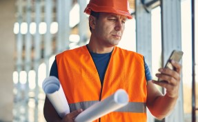 man in hardhat with blueprints